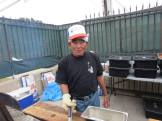 Volunteer barbecuing at the Bazaar! Photographed by Eric Takushi,