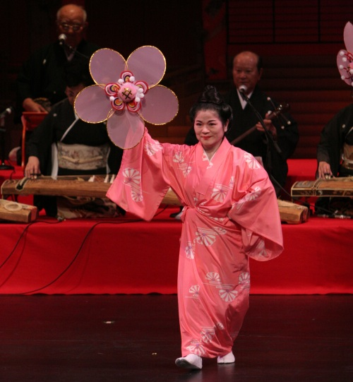 A member of Miyagi-Ryu Nosho-Kai performs a traditional Okinawan folk dance with jikata (live musicians).