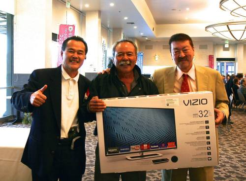 A lucky winner from the 2015 OAA New Year's Party with the HD Smart TV donated by Kamiya Insurance Agency!